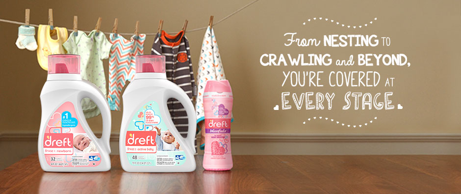 Dreft detergent and scent booster in front of drying baby clothes